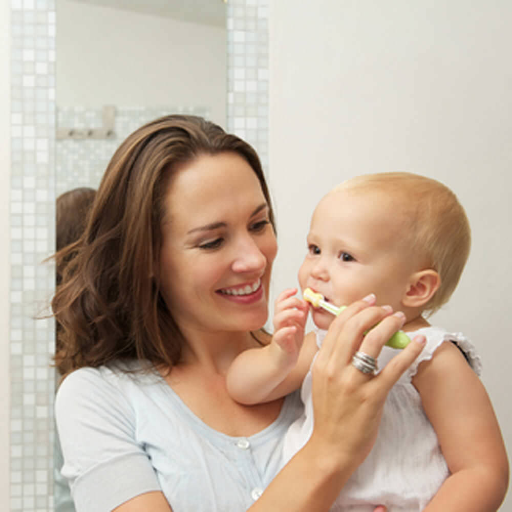 Horizontal portrait of a smiling mother teaching cute baby how to brush teeth with toothbrush